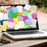 A laptop with post-its stuck on